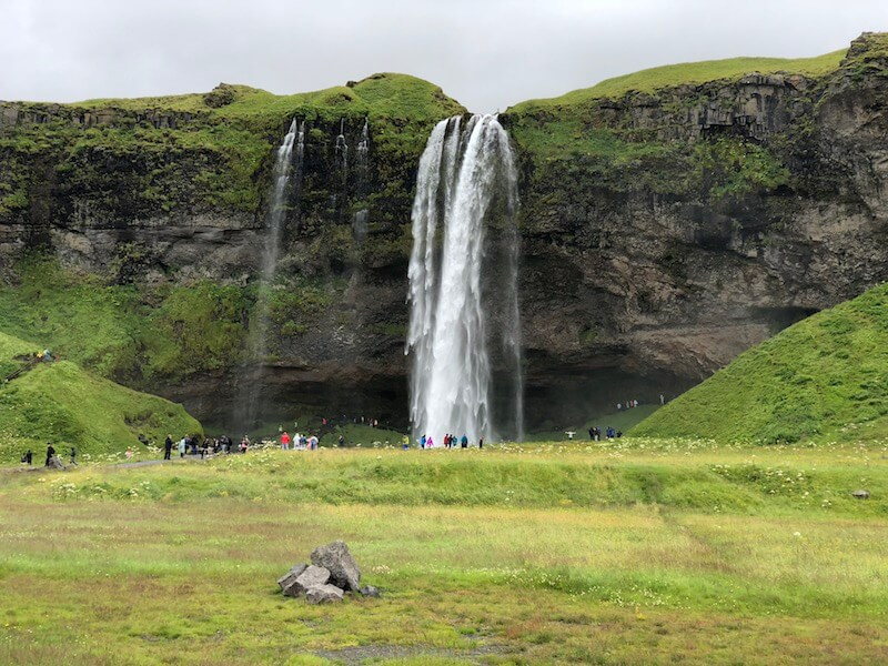 Small waterfall coming over mossy green ledge in distance, with Icelandic green field in forefront