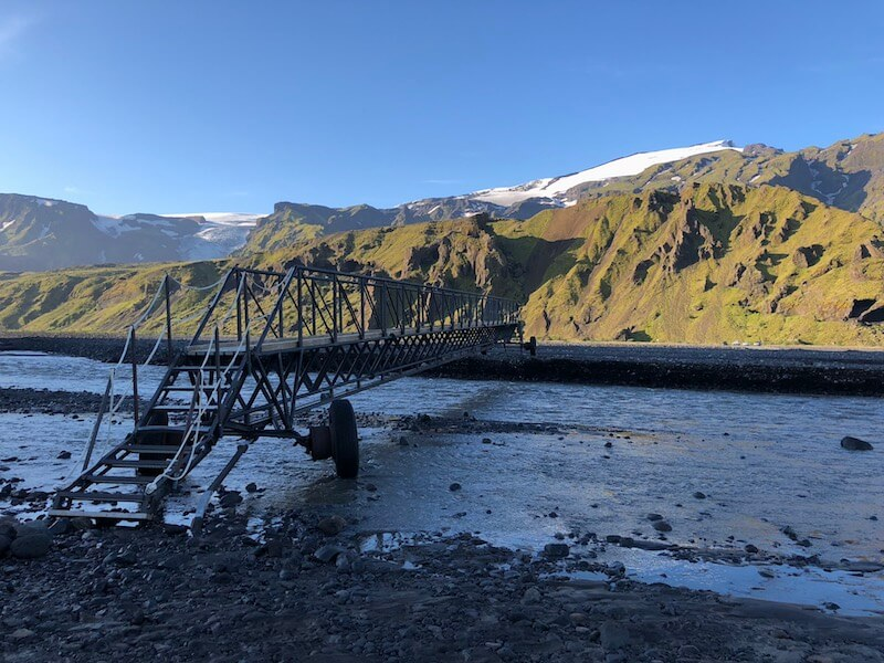 A small metal bridge spanning a shallow body of water to mossy, green Icelandic hills