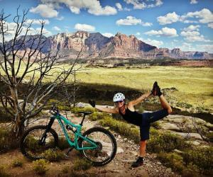 Woman standing next to mountain bike in a field doing the dancer yoga pose