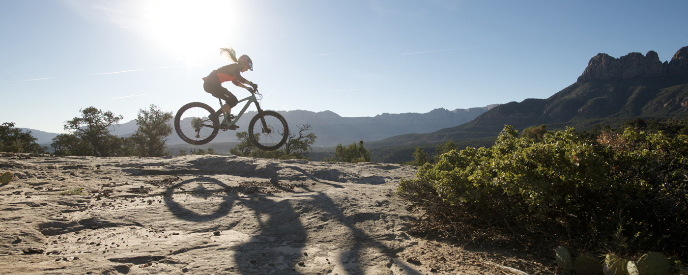 Woman riding mountain bike across desert rock under blue sky and sun