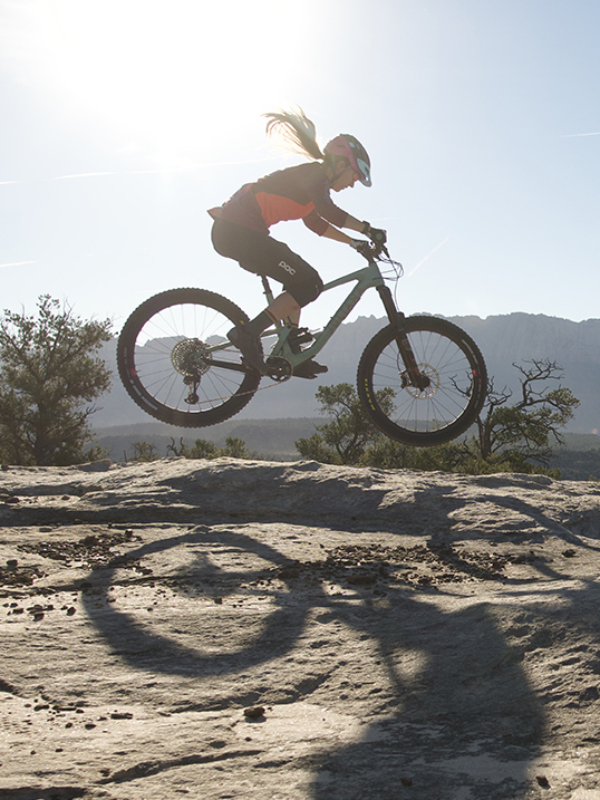Woman riding mountain bike across desert rock under blue sky and sun