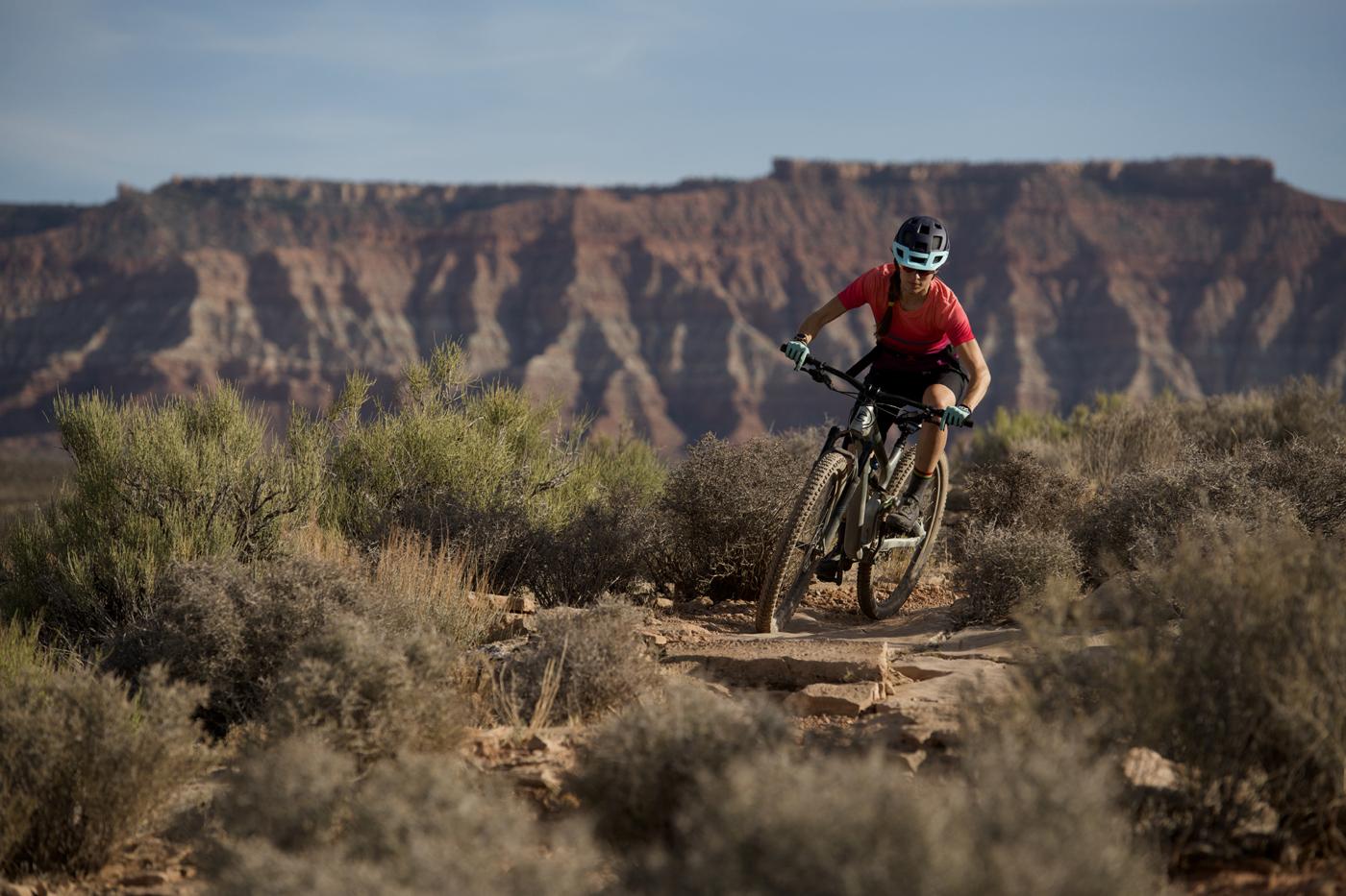 Woman in red shirt riding mountain bike