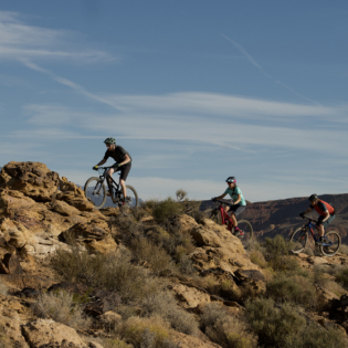 Three people riding mountain bikes over rocky desert terrain in Nevada, with bright blue sky overhead.