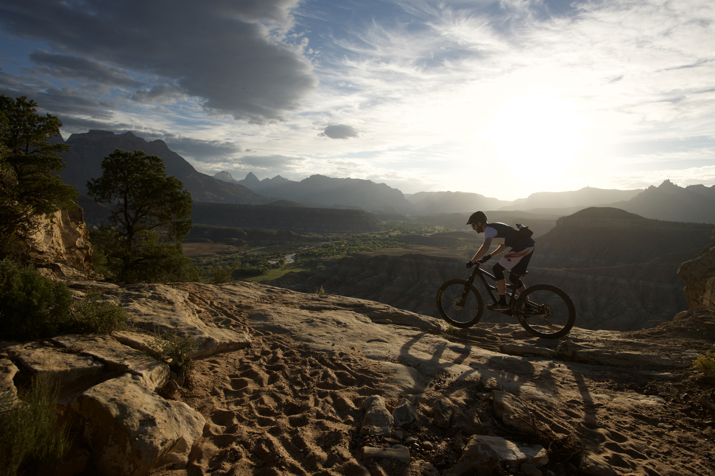 Mountain biker riding across rocky terrain in foreground, with sunsetting over tall rock formations and desert in the background