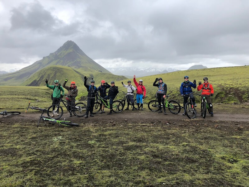Group photo of mountain bike riders and guide standing in the middle of a green, mossy Icelandic field