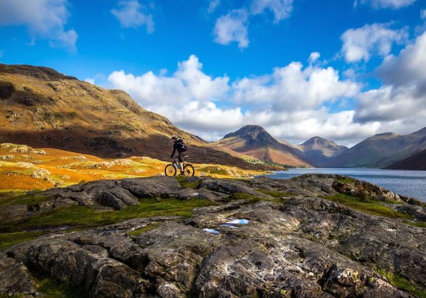 Mountain Biker riding across rocky hills with blue sky over head