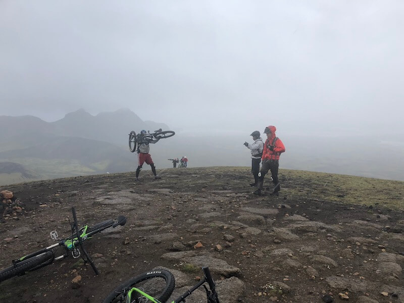 Mountain Bikers standing on flat dirt, carrying bikes in the fog with hills in background