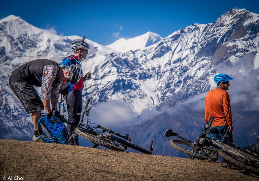 Three mountain bikers standing and looking around with their bikes lying on the ground, surrounded by snow covered mountains in Nepal