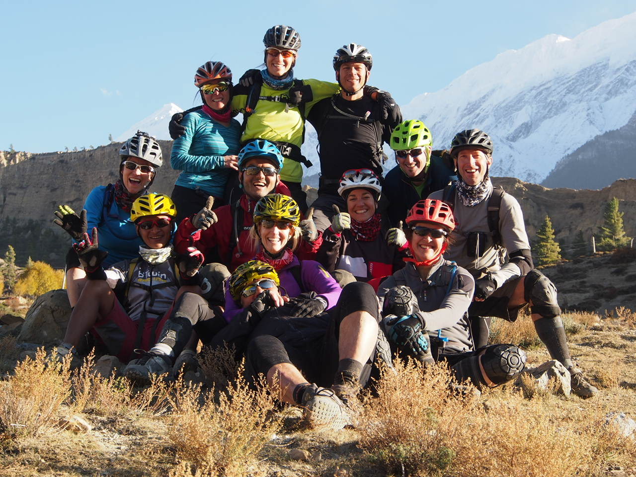Group of smiling men and women in mountain bike gear posing together for photo on a field with mountains in the baackground