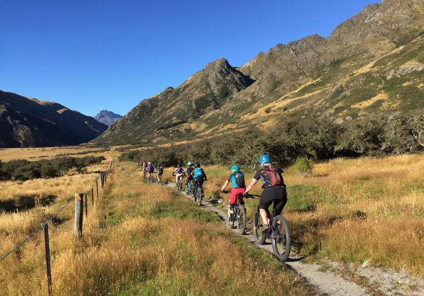 8 mountain bikers riding in line on a trail through grassy landscape surrounded by mountains on Rocky Mountain Rambler Tour