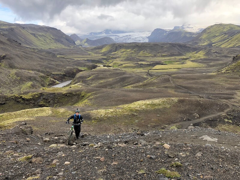 Mountain Biker carrying her bike across remote, rocky terrain with green, mossy landscape of Iceland in the distance