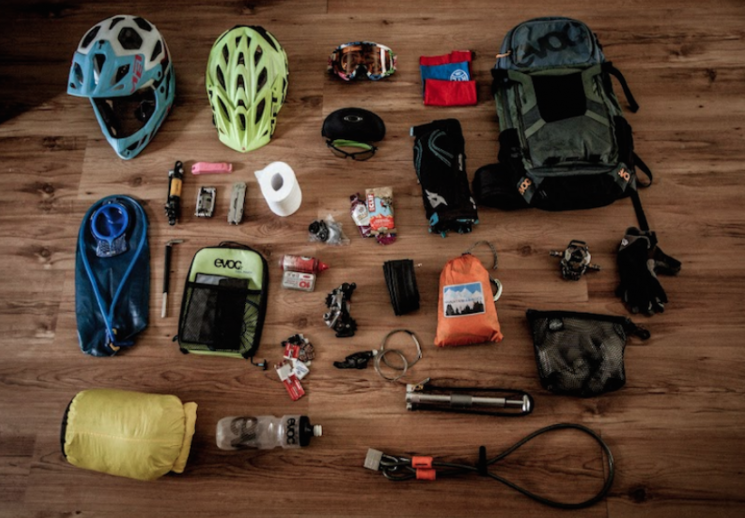Overhead view of items for mountain bike trip laid out on the floor, including things like mountain bike helmet, backpacks, flashlight, etc.