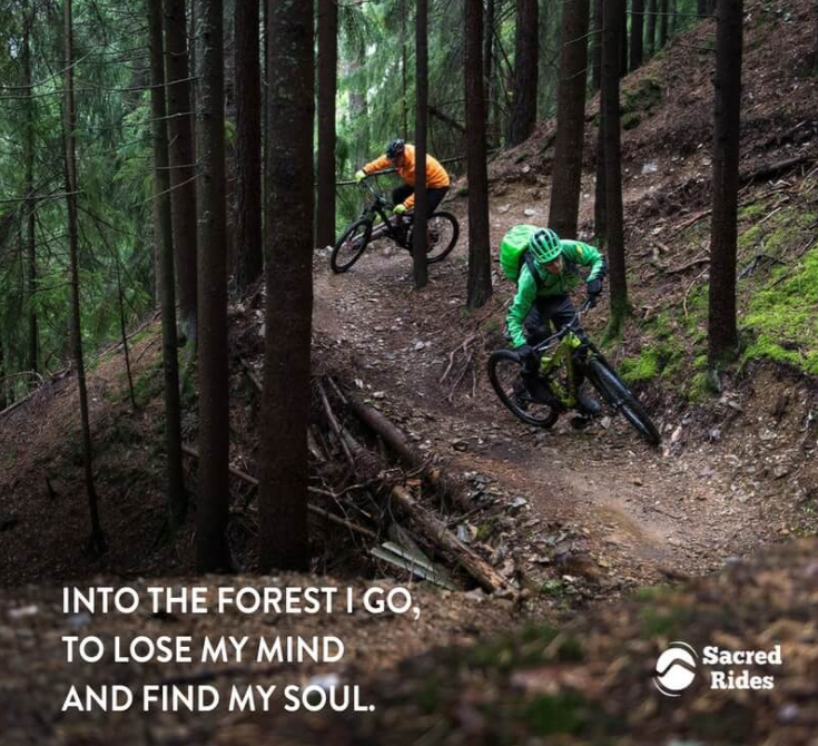 """Two people riding mountain bikes quickly on trail through the woods with the caption, """"Into the forest I go, to lose my mind and find my soul."""""""