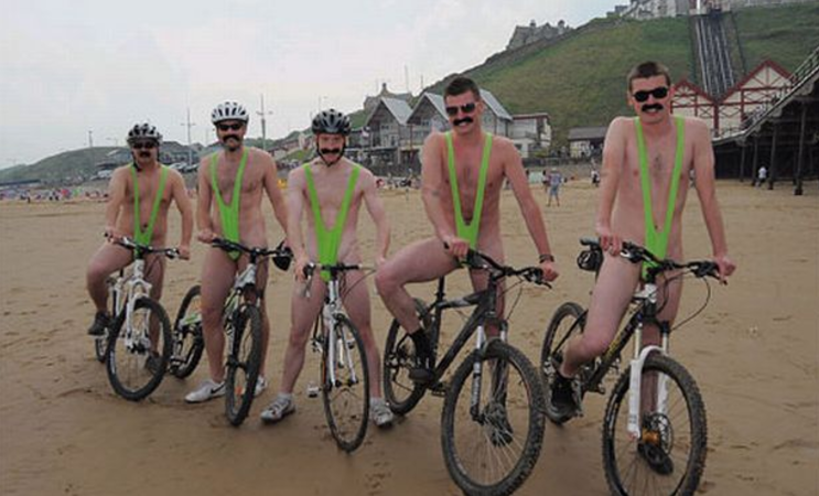 Five men on bikes at the beach, wearing bright green thong bathing suits