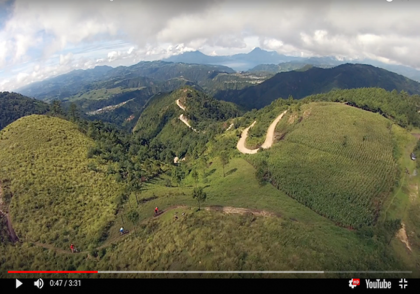 Screenshot of YouTube Video showing rolling green mountains under a cloudy sky in Guatemala