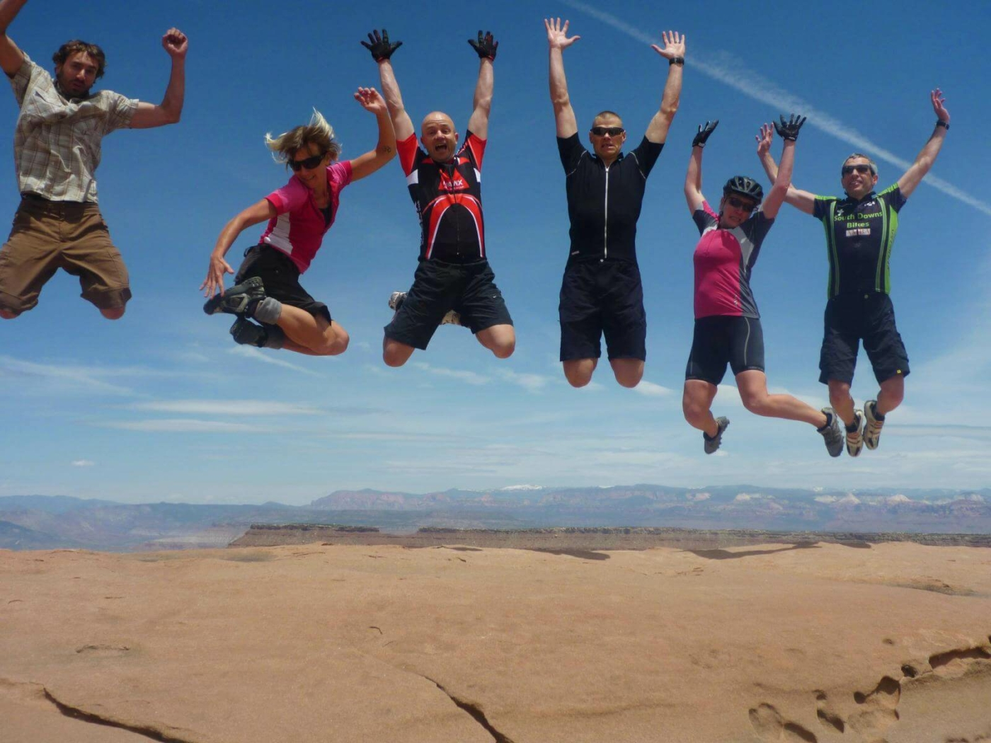 Several people in biking gear leaping into the air and smiling over a reddish brown dry earth landscape in Utah
