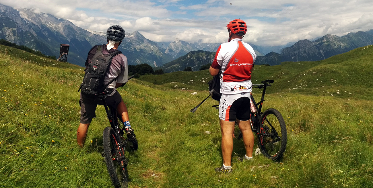 One person sitting on a mountain bike and one person standing next to a mountain bike in a green field looking out towards mountains