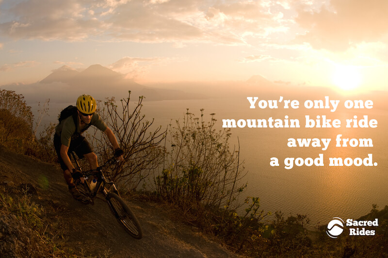 """Man mountain biking along a ridge line at sunset near the ocean with the words, """"You're only one mountain bike ride away from a good mood."""""""