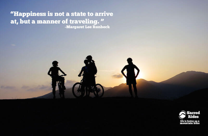"""Silhouettes of three mountain bikers on a hilltop at sunset with the words, """"Happiness is not a state to arrive at, but a manner of traveling. - Margaret Lee Runbeck"""