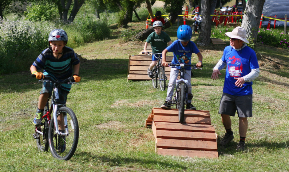 Several Kids Riding Mountain Bikes on Small Ramps in a Field With an Adult Standing Next to One Ramp to Give Them Guidance