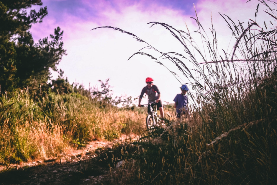 Man on Mountain Bike Talking to Kid Next to Him Wearing a Mountain Bike Helmet