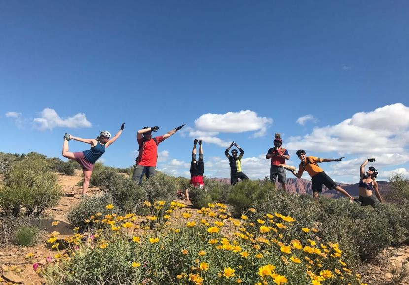Several people wearing mountain bike gear, standing in a field doing different yoga poses