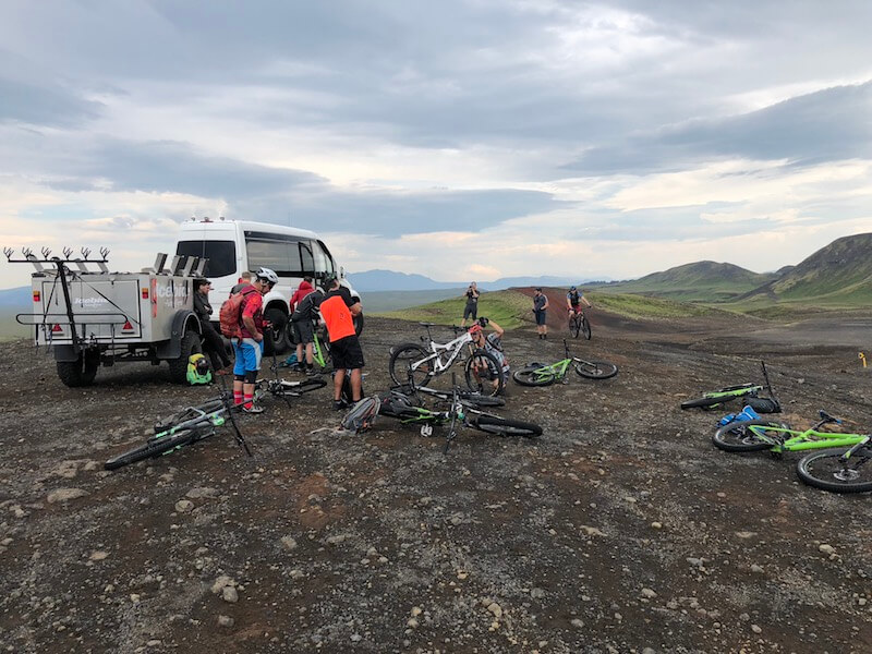 People unloading mountain bikes off a white van in a field in Iceland
