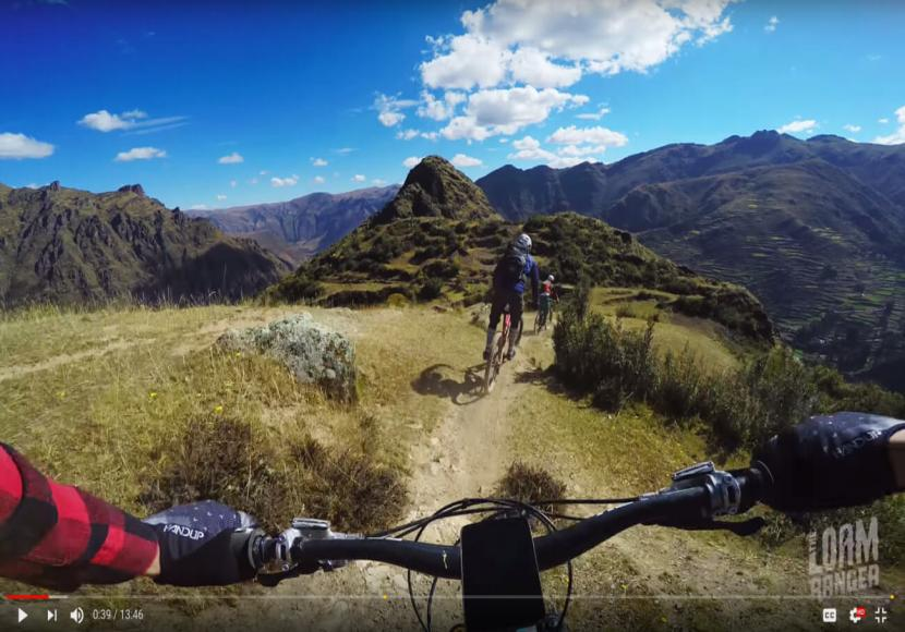Screenshot from a video taken from viewpoint of a mountain bike rider looking ahead to other riders and mountains on trail in Peru