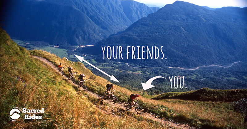 """Five mountain bikers riding in a line on a trail through a mountain valley with an arrow pointing to one person that says """"You"""" and another that says """"your friends"""""""