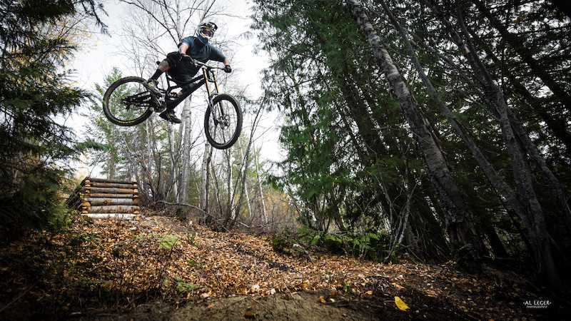Mountain Biker in mid-jump off a ramp made of small logs in the woods