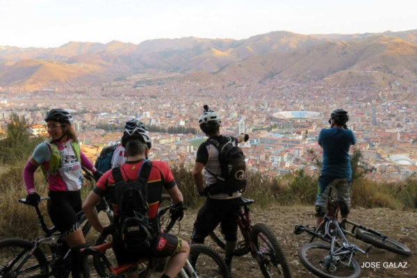 Five mountain bikers sitting on bikes high up on a hill, looking out over the red tile roofs in the valley below