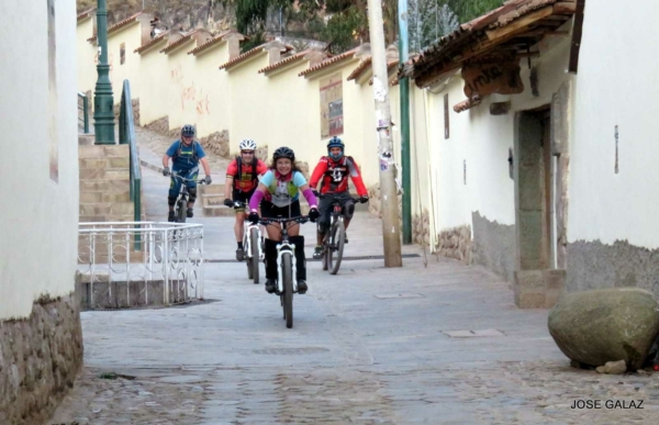 Four mountain bikers riding up cobblestone street along pale yellow wall in a Peruvian village