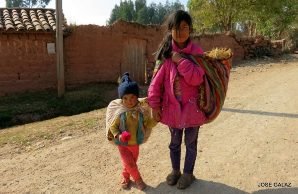 Two Peruvian girls, around ages 10 and 4, holding hands on dirt road in village outside of red brick wall