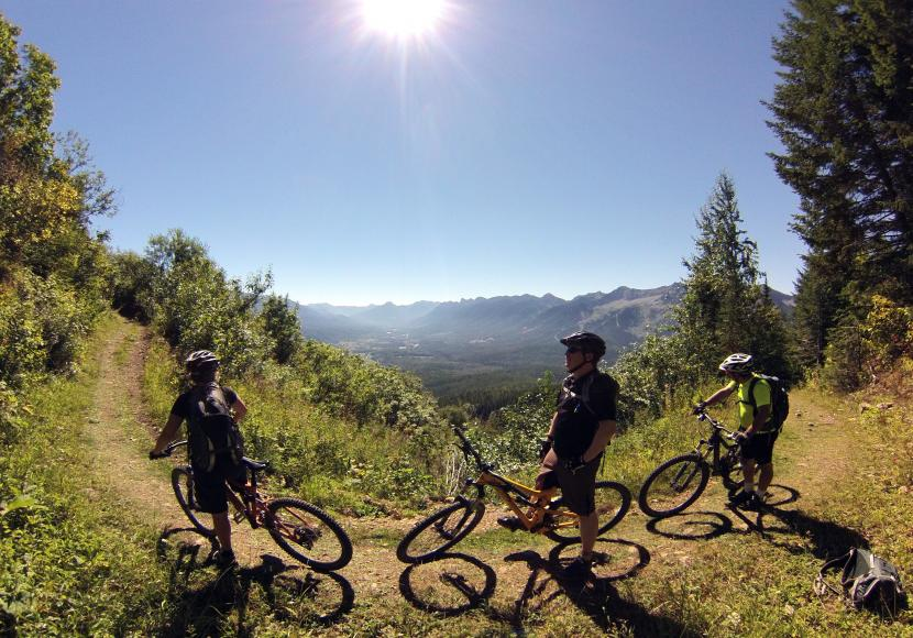 Three people sitting on mountain bikes on a path high over a mountain valley