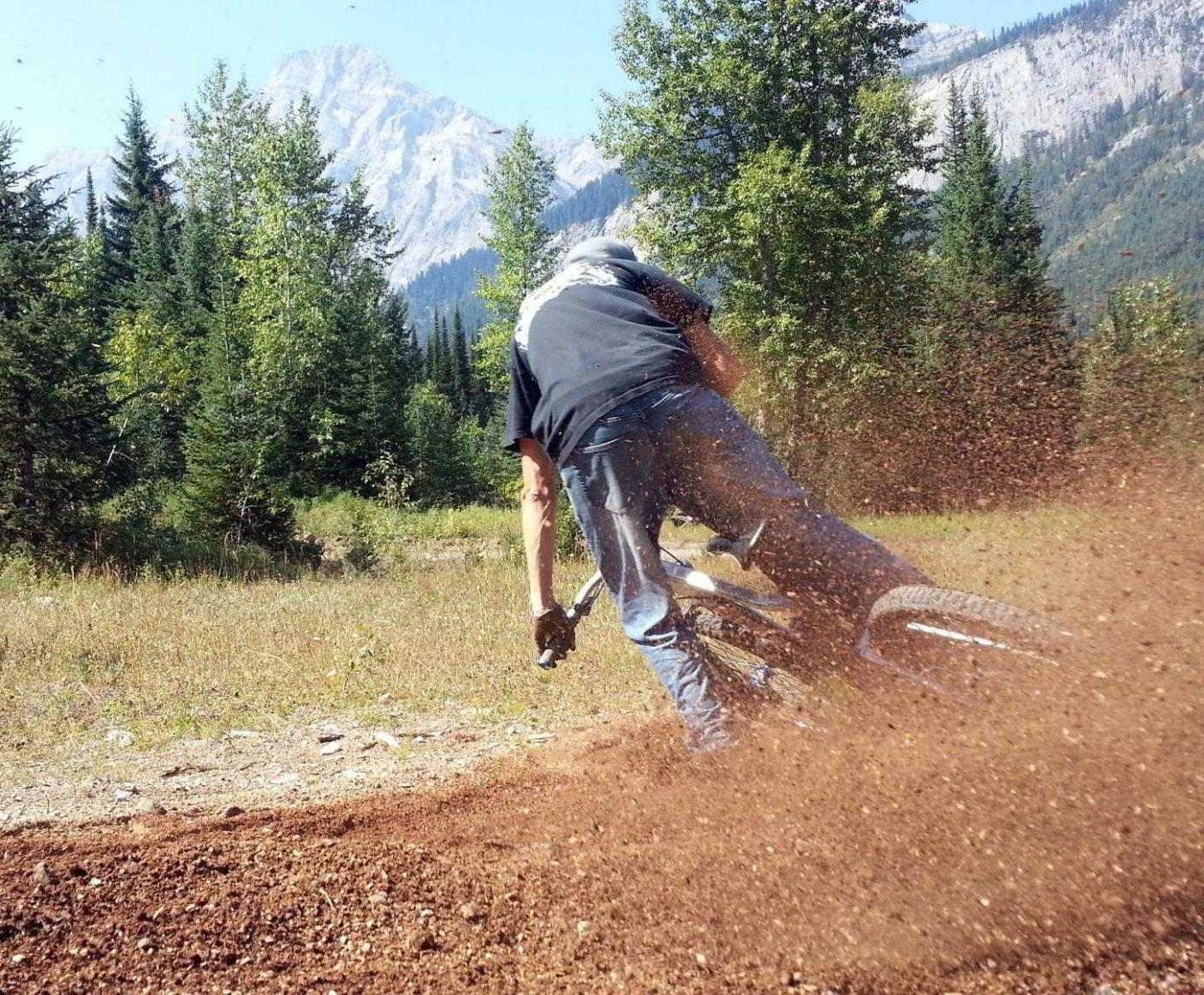 Man taking fast turn on mountain bike, kicking up dirt with back wheel towards camera