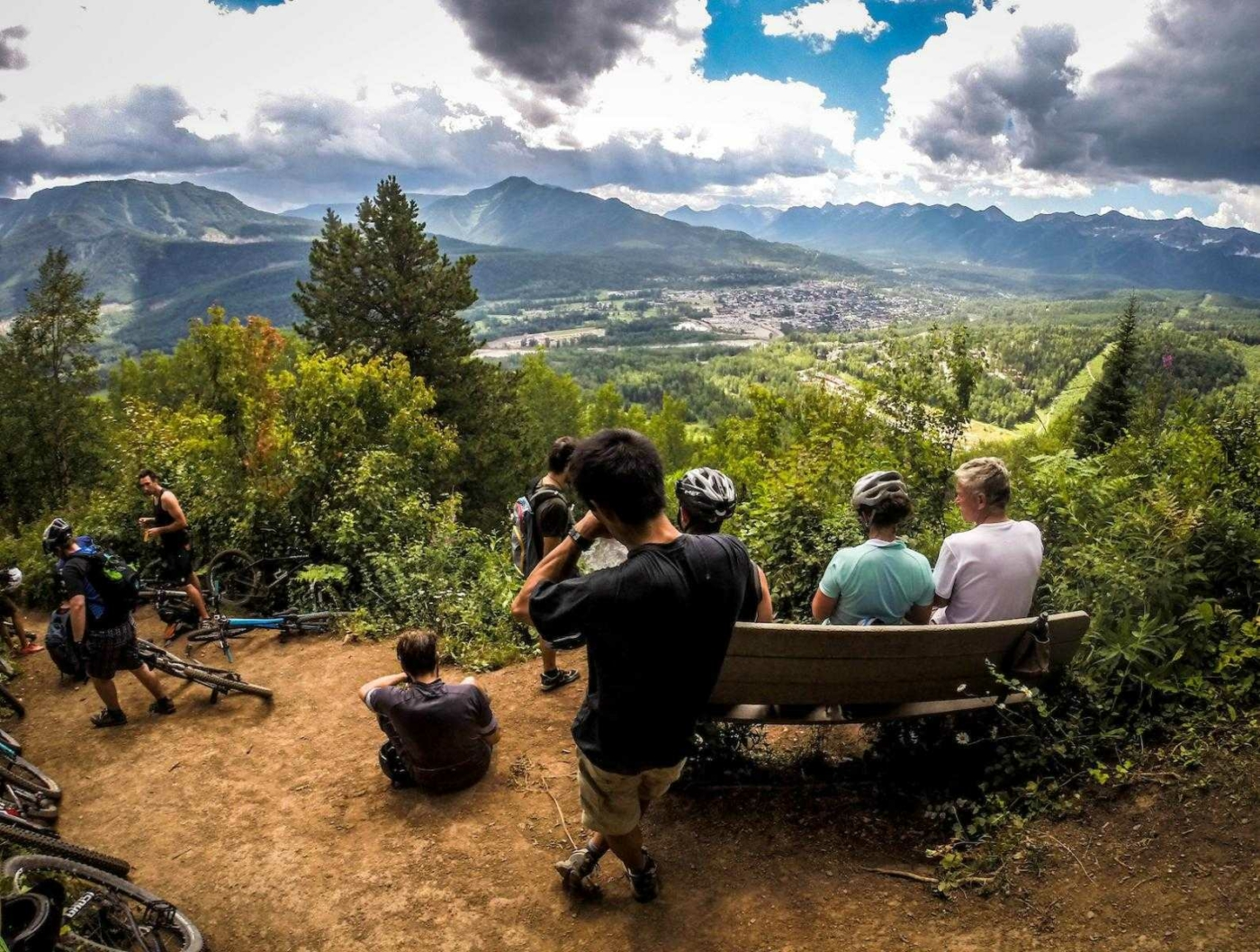 Several people resting on benches and on the ground with mountain bikes, on high viewpoint looking over green mountain valley