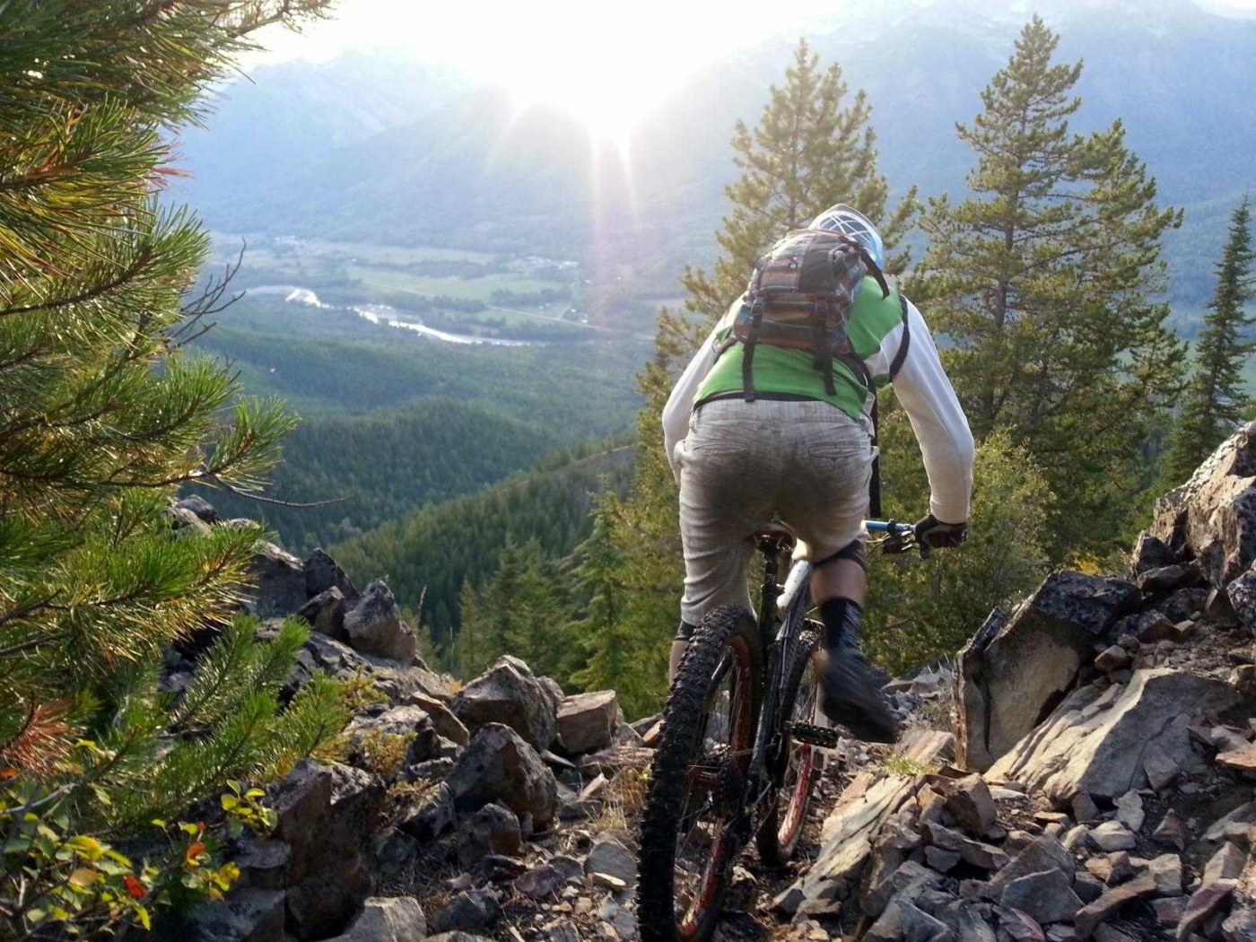 Mountain Biker riding away from camera on rocky trail at top of steep drop overlooking green mountain valley with bright sun overhead