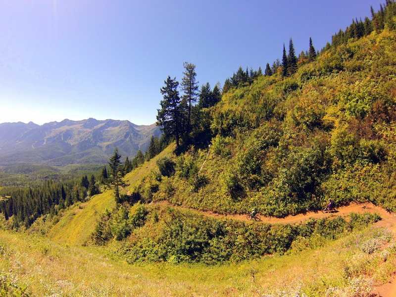 Two mountain bikers on a narrow, winding trail cutting horizontally across a steep, green mountainside