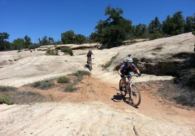 Two people riding mountain bikes across pale desert rock terrain with bright blue sky over head