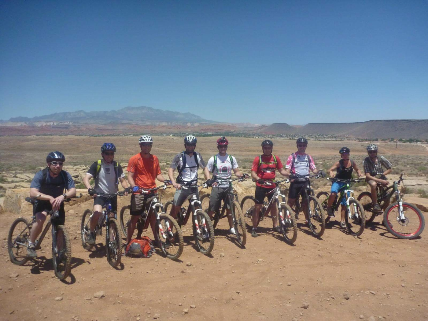 9 people lined up side-by-side sitting on their mountain bikes in rock desert landscape