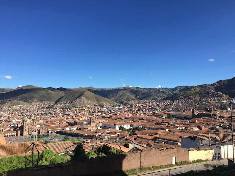 Looking out over small houses with red rooftops, with rolling hills in the background, in Cusco Peru.