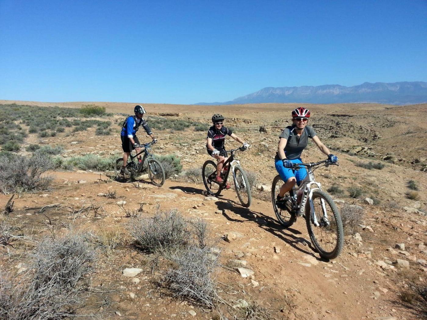 Three people mountain biking in a line across rocky desert terrain