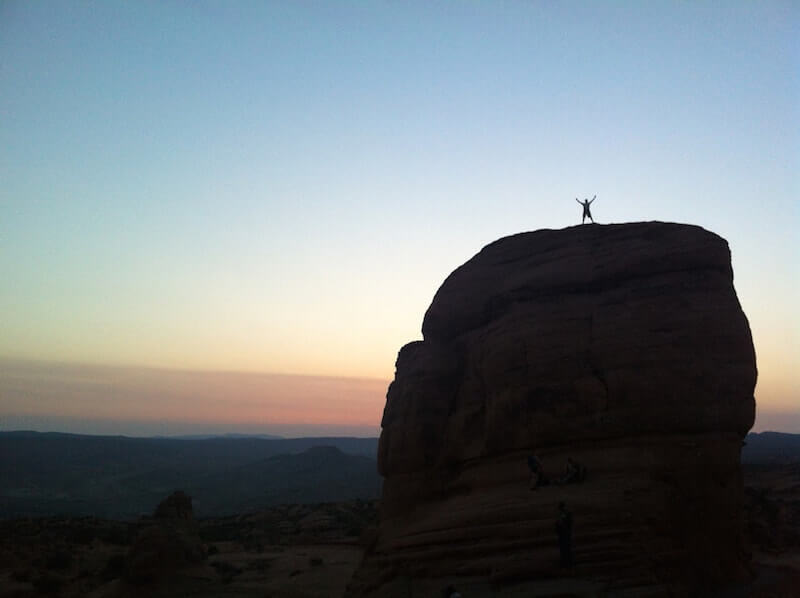 Silhouette of person standing on massive boulder the height of a house, with sunset and fading orange and red on the horizon
