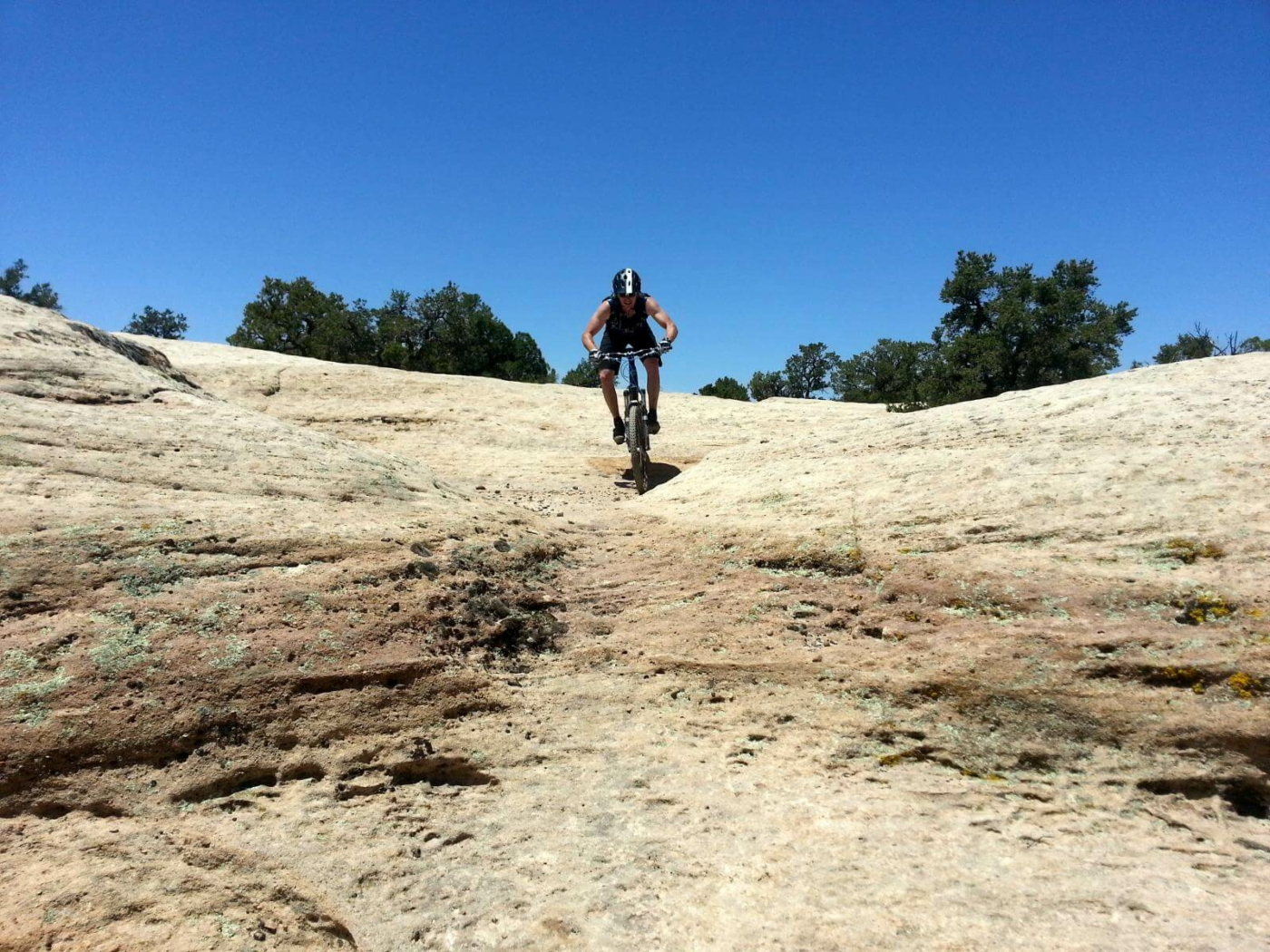 Mountain biker coming down a sandstone hill in Utah with bright blue sky overhead