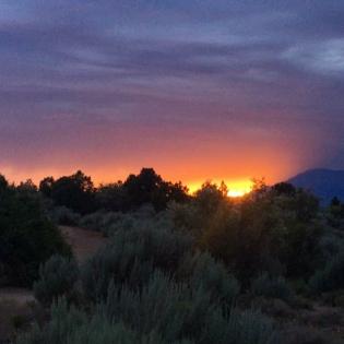 Sun peeking over desert-grass covered hill as it sets under a purplish sky