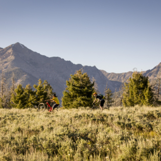 Mountain biker in middle ground riding across grassy field with field in foreground and low mountain peaks in background