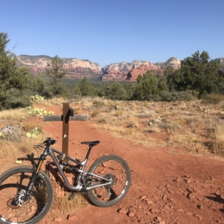 Mountain bike parked in middle of red dirt trail crossing with small wooden cross-shaped sign in middle