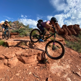 Two women on mountain bikes riding fast down red desert rock under blue sky