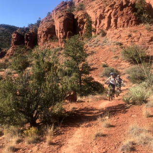 Two people on mountain bikes riding down slight incline towards viewer on red desert trail, with red rock towers behind them