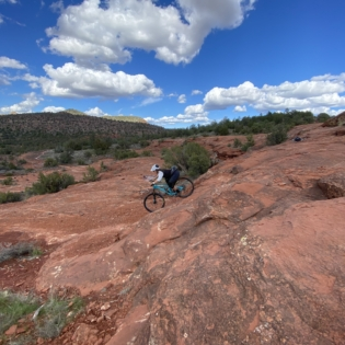 Biker on blue mountain bike riding down red boulders surrounded by desert with blue sky overhead